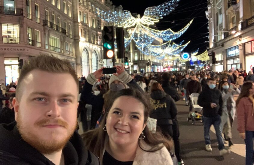Couple (male and female) in London underneath Christmas Lights